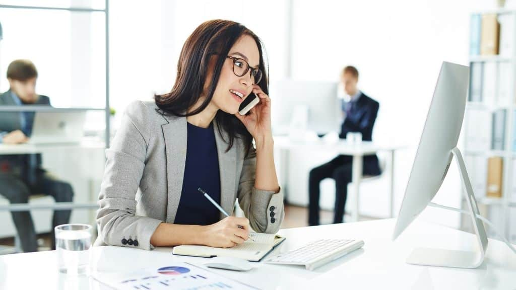 focused woman in office on phone writing