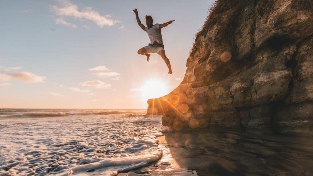 man jumping off rock into ocean at sunset