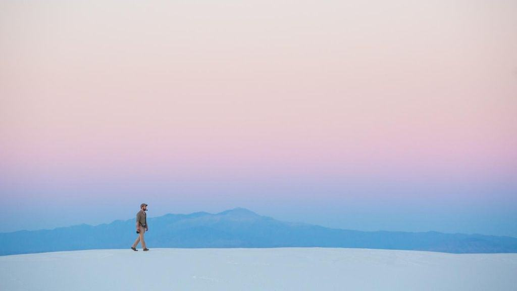 person walking flat land near mountain sunrise
