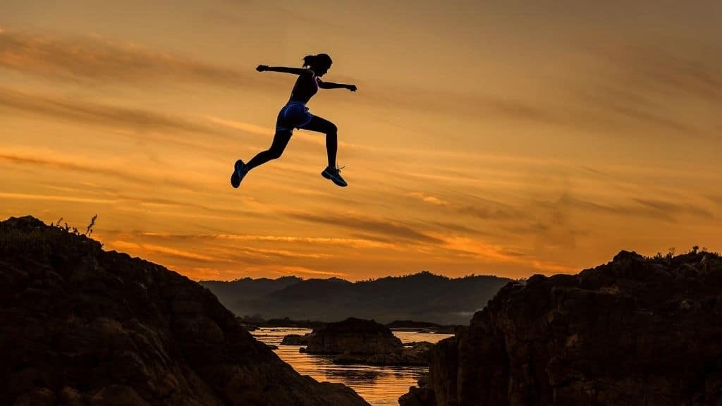 person on adventure leaping between rocks sunset