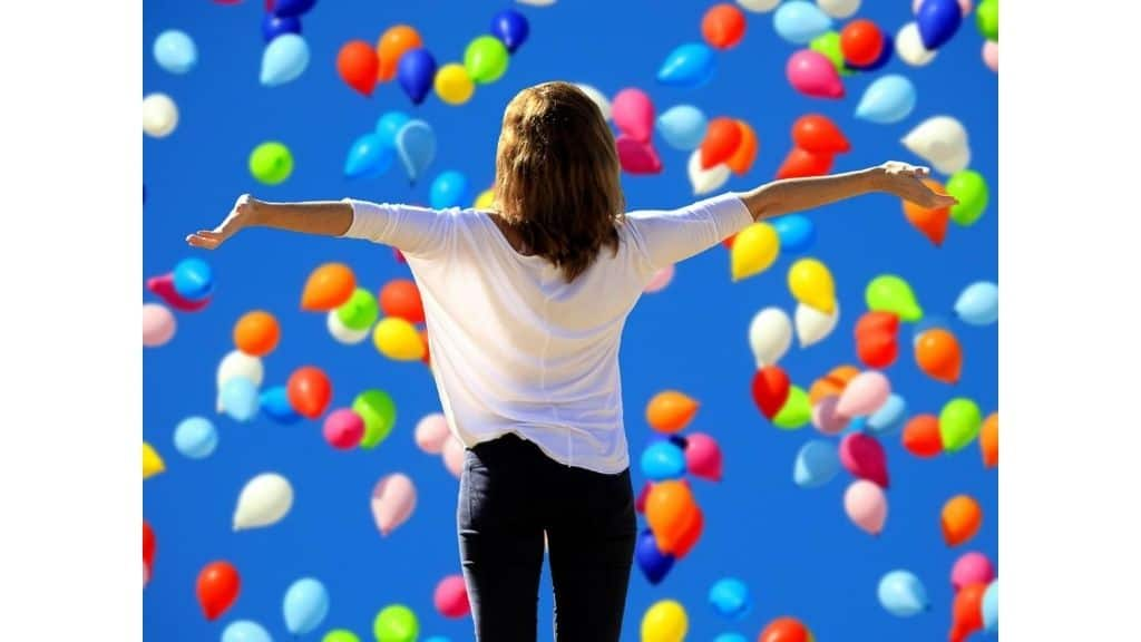 happy woman in black and white surrounded by colorful balloons and blue sky