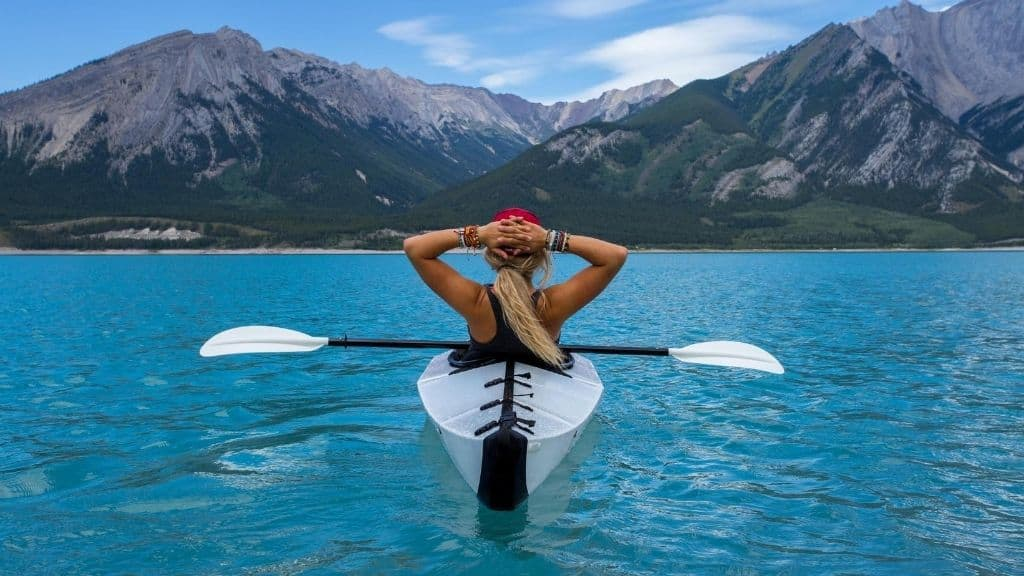proud woman in kayak on blue lake facing mountain