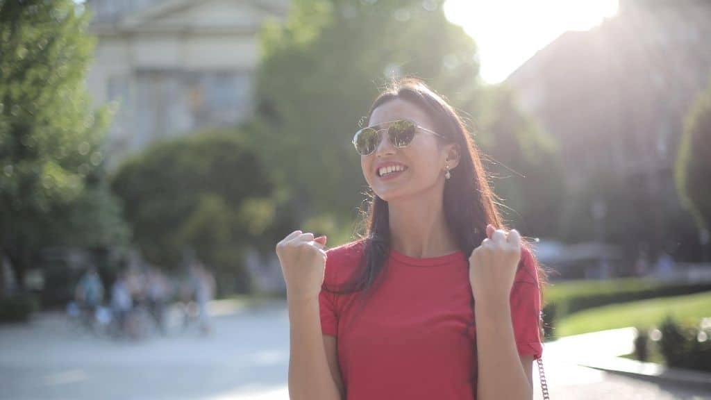 successful woman outside in sunglasses and red dress happy