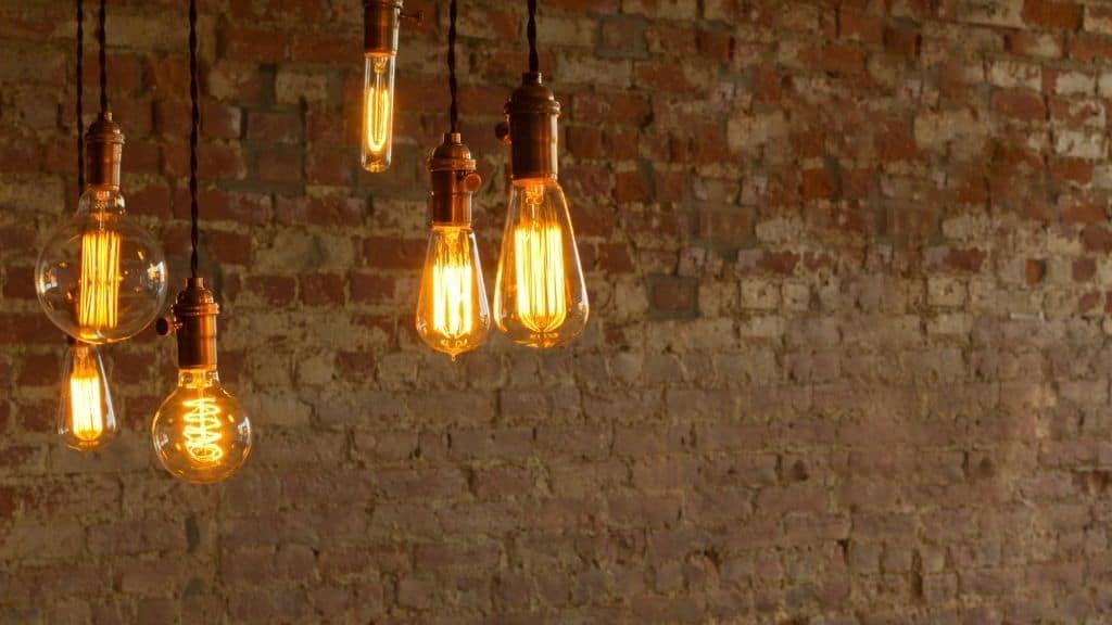 warm lightbulbs hanging against brown brick wall
