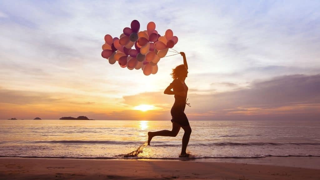happy woman running on beach with balloons sunset