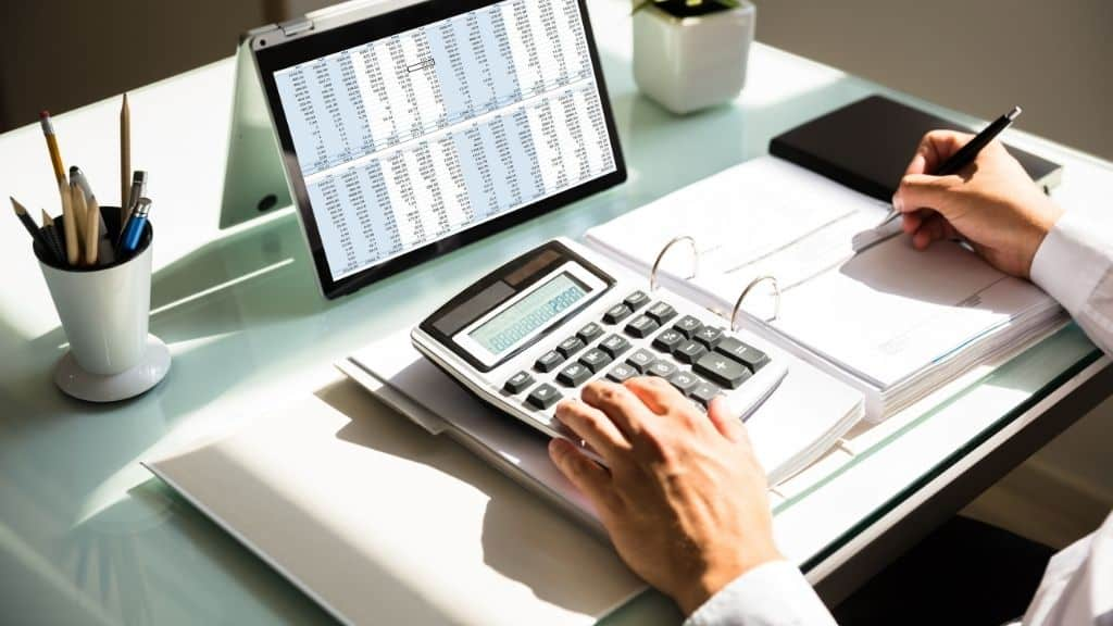 hands on desk doing personal finance calculations with tablet calculator