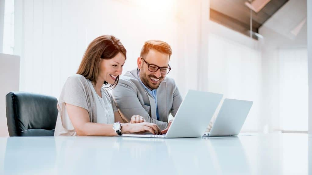 man and woman with laptops at table