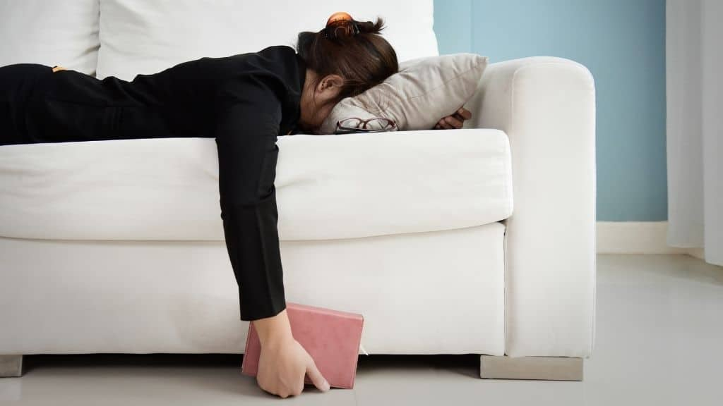 woman exhausted on white couch with pink tablet